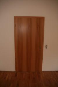 Buche-Echtholztür mit matt verchromtem Türdrücker auf Kirschparkett